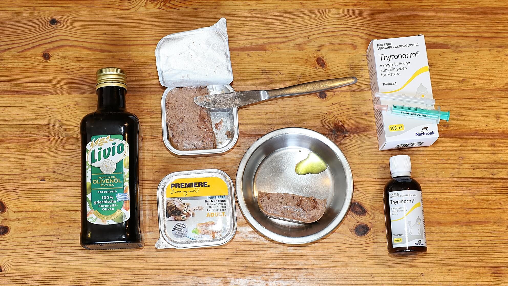 CBD-Öl, Katzenfutter und Thyronorm auf dem Tisch – kranke Katze Dgani wird ohne das nicht mehr alt
